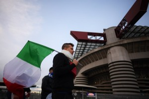 An Italian supporter holds a flag as he arrives at the San Siro Stadium before the FIFA World Cup 2018 qualification football match between Italy and Sweden, on November 13, 2017 in Milan. / AFP PHOTO / MARCO BERTORELLO